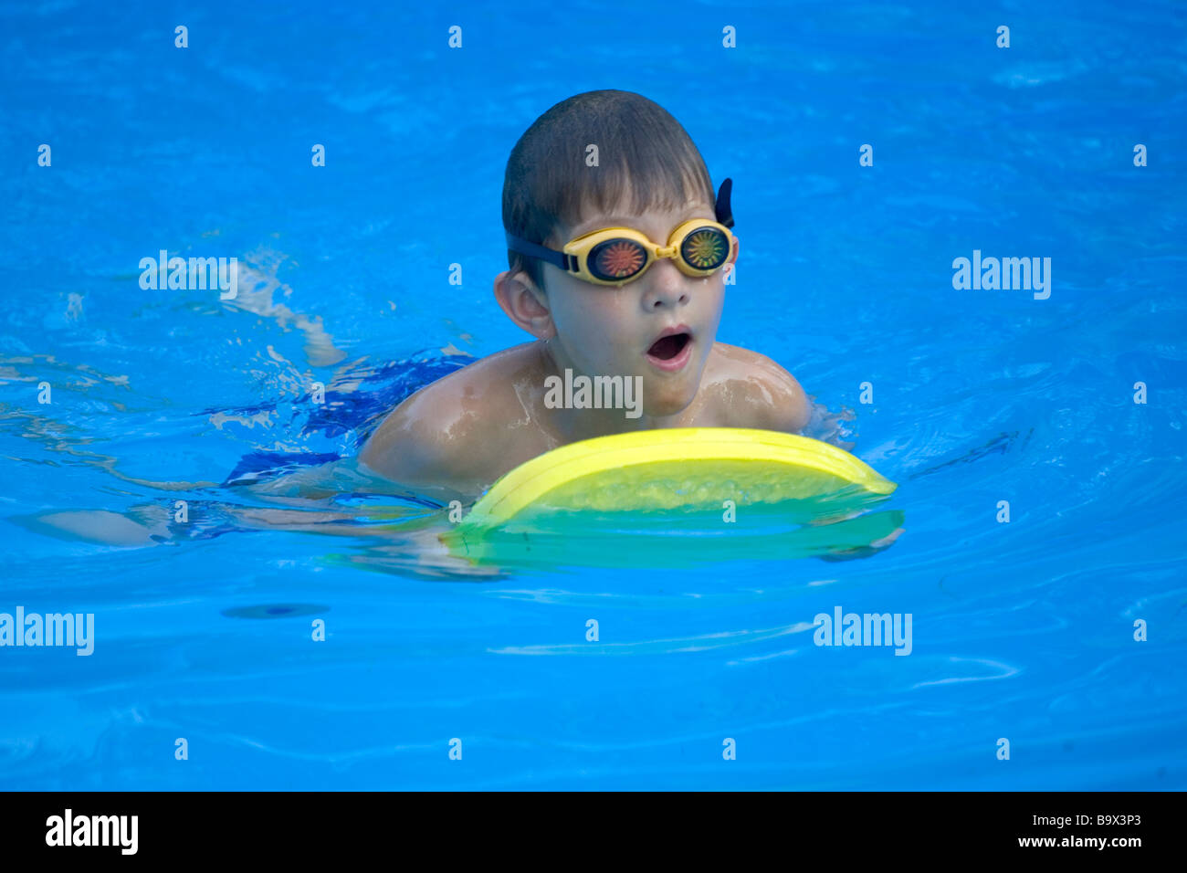 9 year old boy swimming in pool - Stock Image