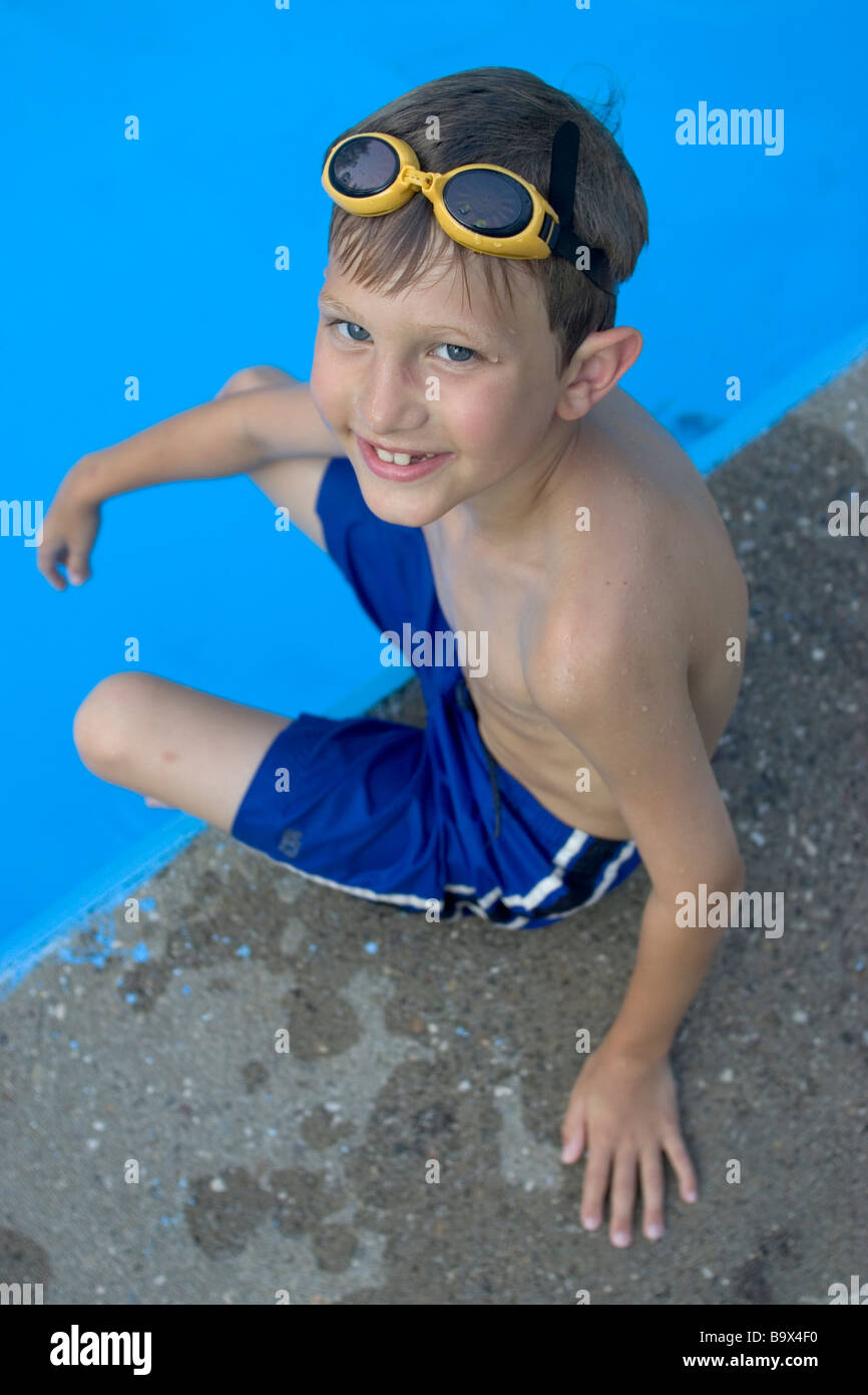 Portrait of 9 year old boy sitting at the edge of the swimming pool - Stock Image