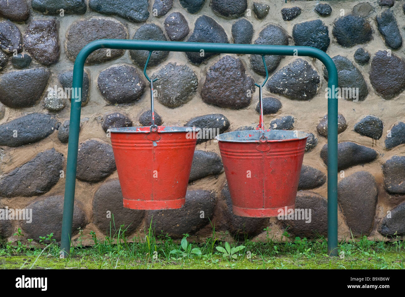 Red fire buckets hanging outside a cottage in the Injisuthi National Park in the Drakensberg mountains. Kwazulu Natal, South Africa Stock Photo