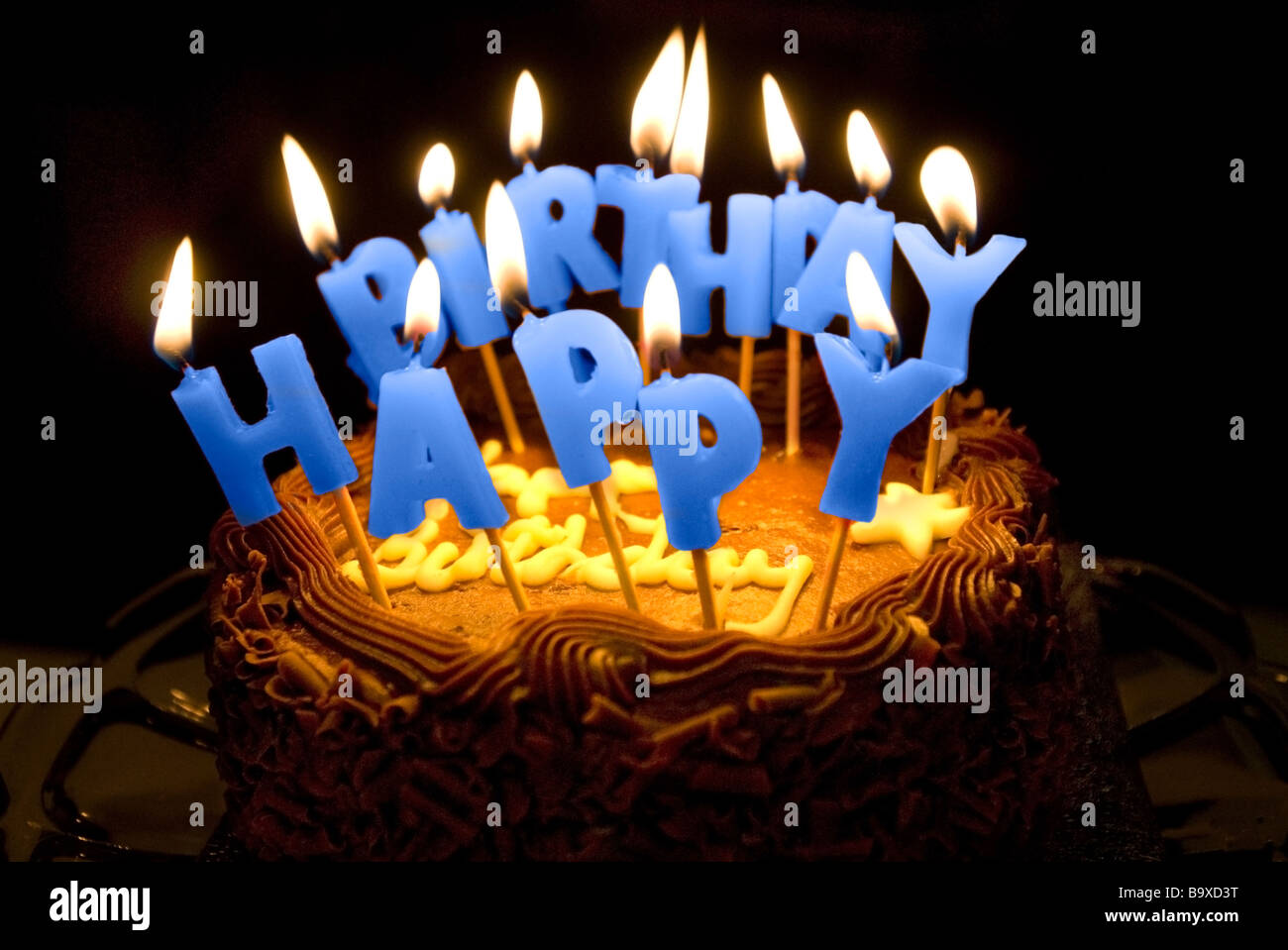 A Birthday Cake With Lighted Letter Candles Spelling Happy