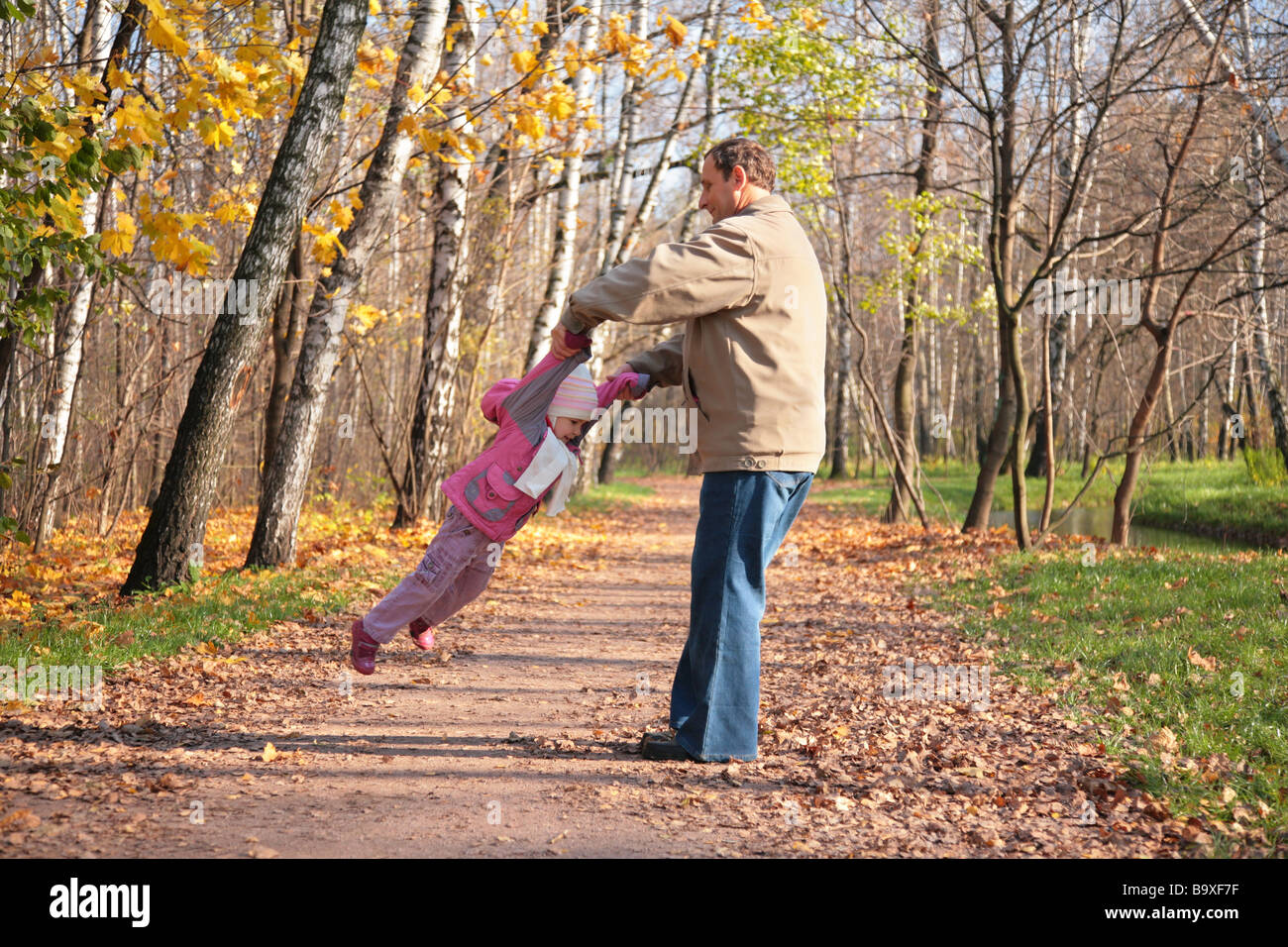 Grandfather rotates  granddaughter  in wood in autumn - Stock Image