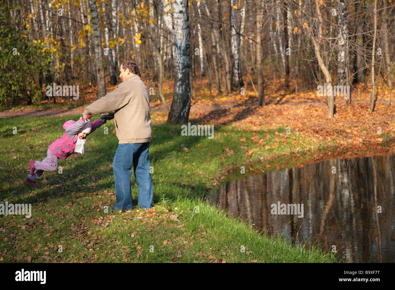 Grandfather rotates  granddaughter  in wood in autumn near pond - Stock Image