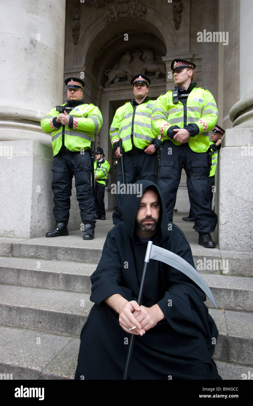 G20 demonstration London row of police officers behind grim reaper - Stock Image