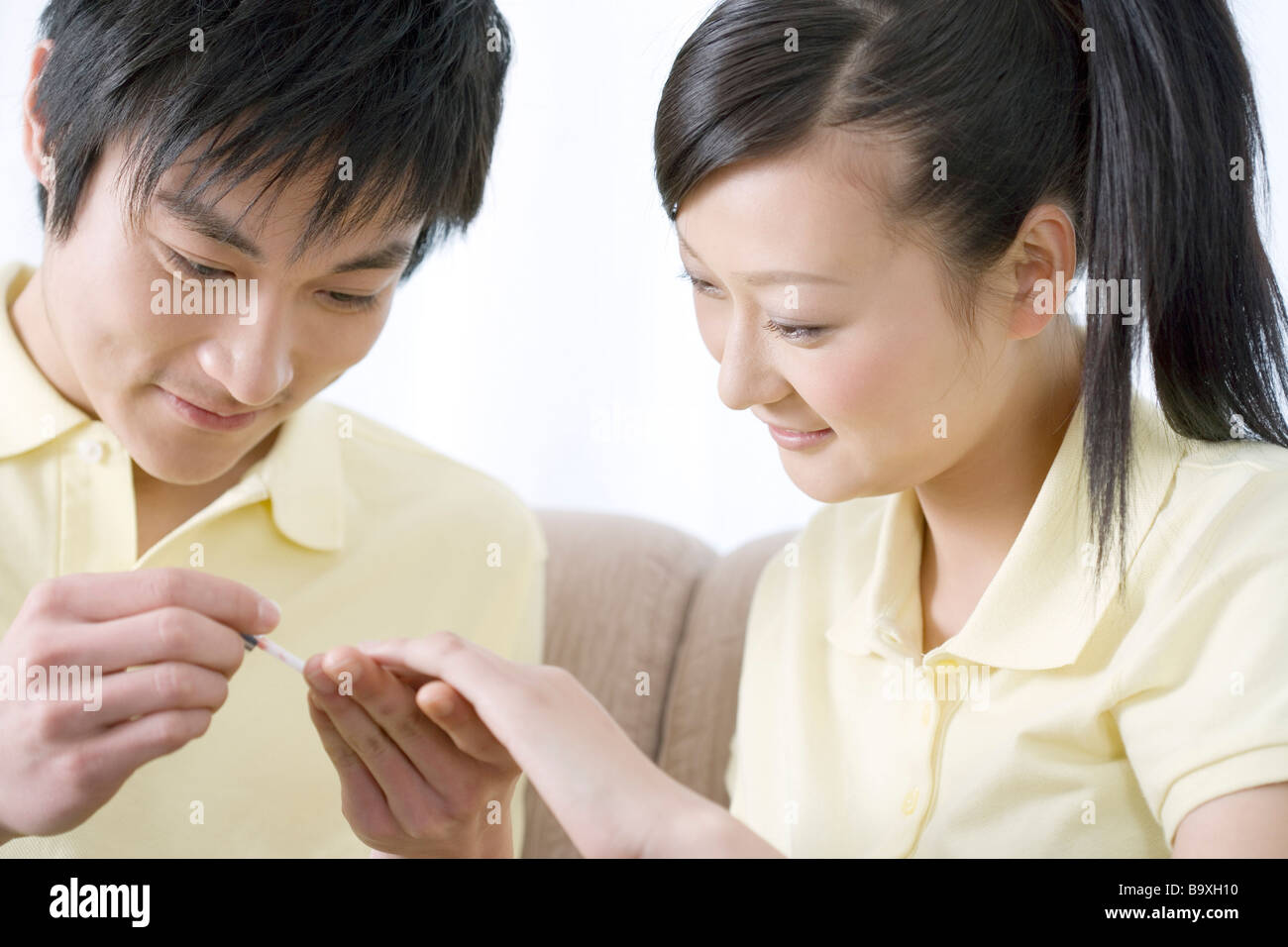 Young man applying nail polish for woman\'s fingernail Stock Photo ...