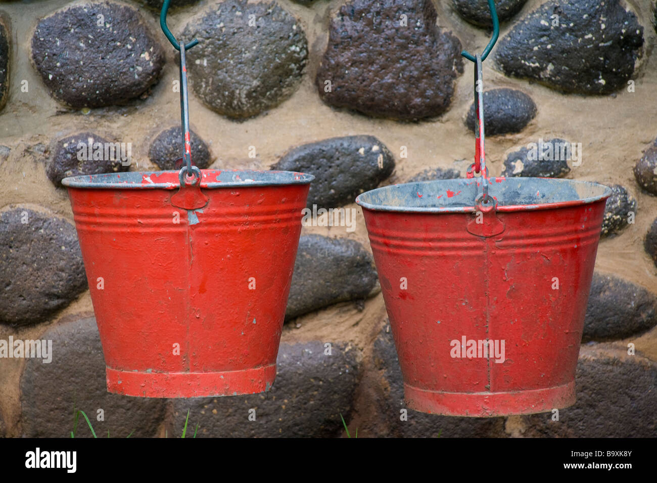 Two red fire buckets hanging outside a cottage in the Injisuthi National Park in the Drakensberg mountains. Kwazulu - Stock Image