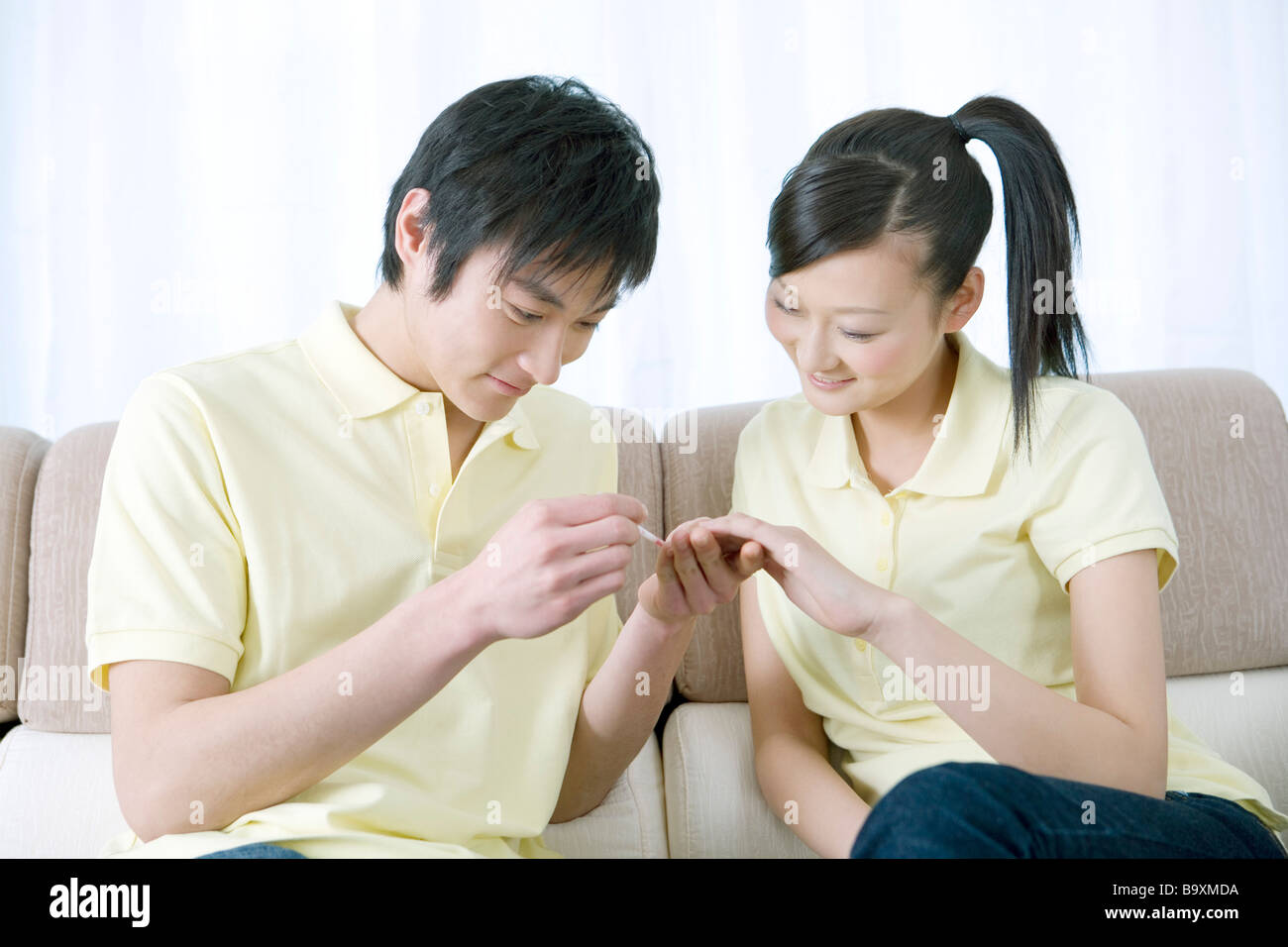 Young man applying nail polish for his girlfriend on sofa smiling ...