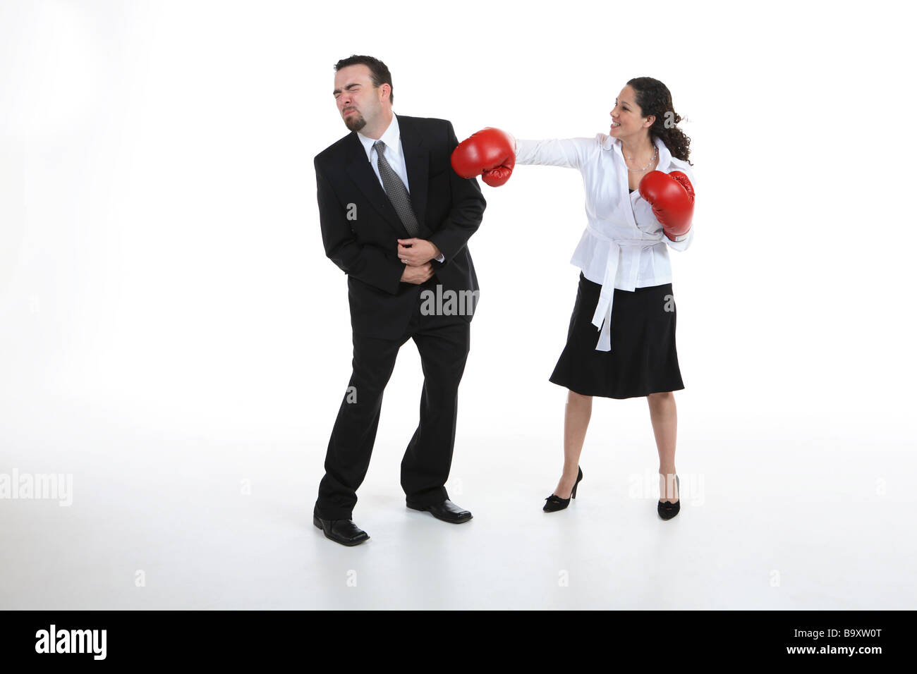 Businesswoman with boxing gloves punching man isolated on white - Stock Image