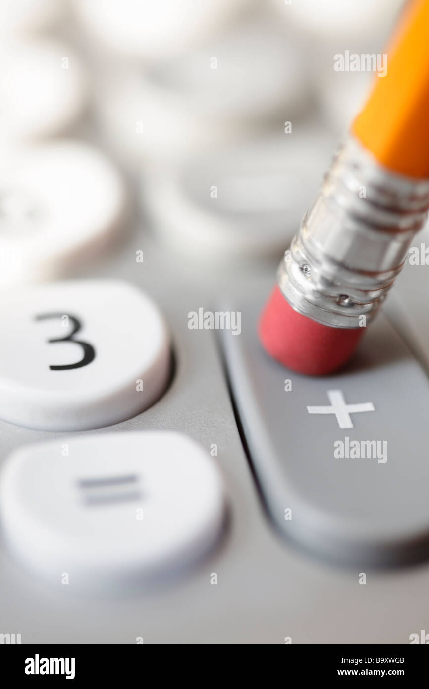 Pencil pushing addition button on calculator - Stock Image