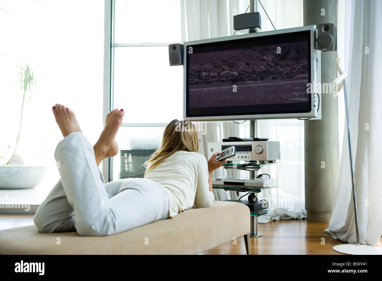 Female lying on chaise longue, watching flat screen television with surround sound - Stock Image