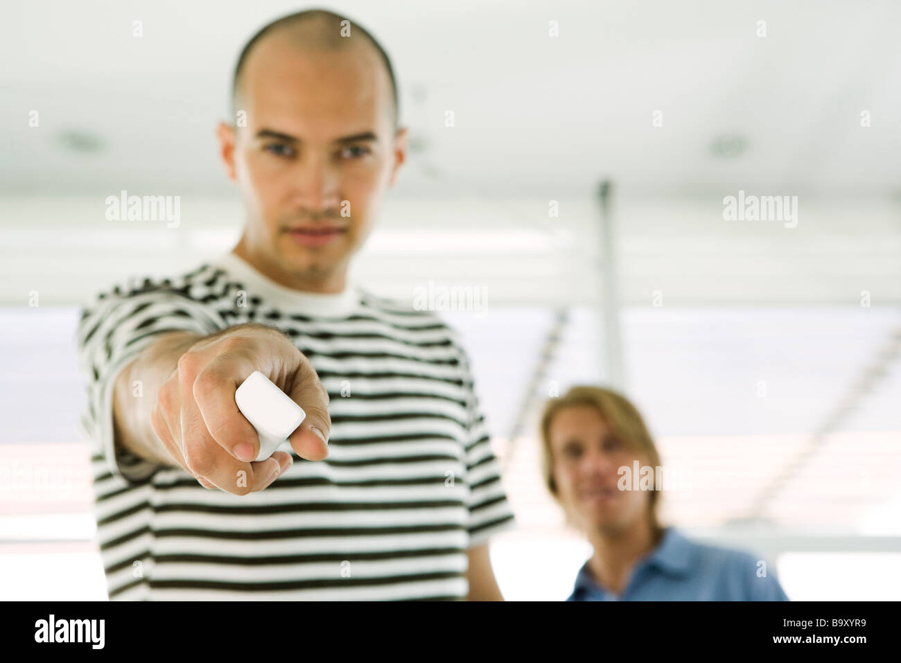 Man holding out wireless remote control, focus on foreground - Stock Image