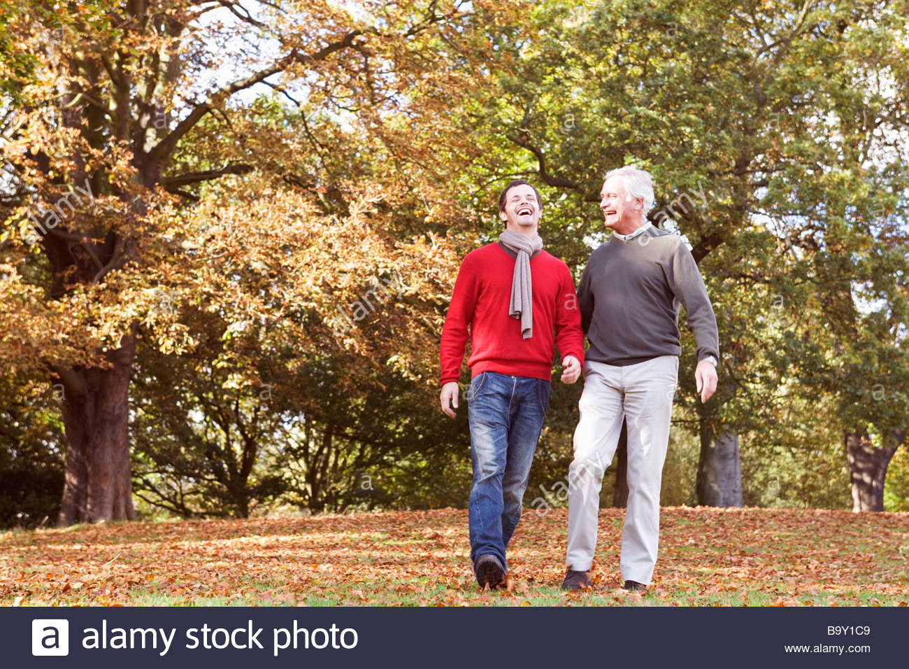 Father and son laughing in the autumn time - Stock Image