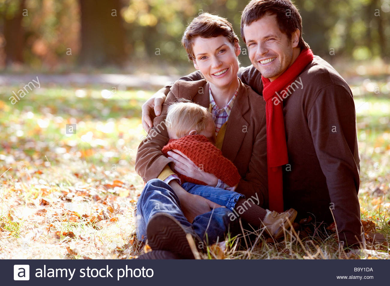 A portrait of a young family sitting on the grass in autumn time - Stock Image