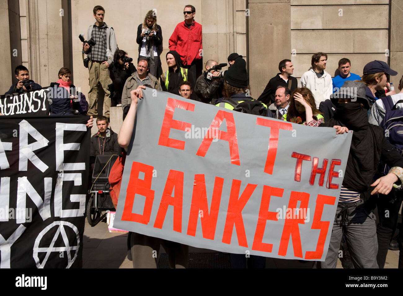 Demonstrators with :Eat The Bankers' placard, at the Bank of England protesting at the G20 summit in London. - Stock Image