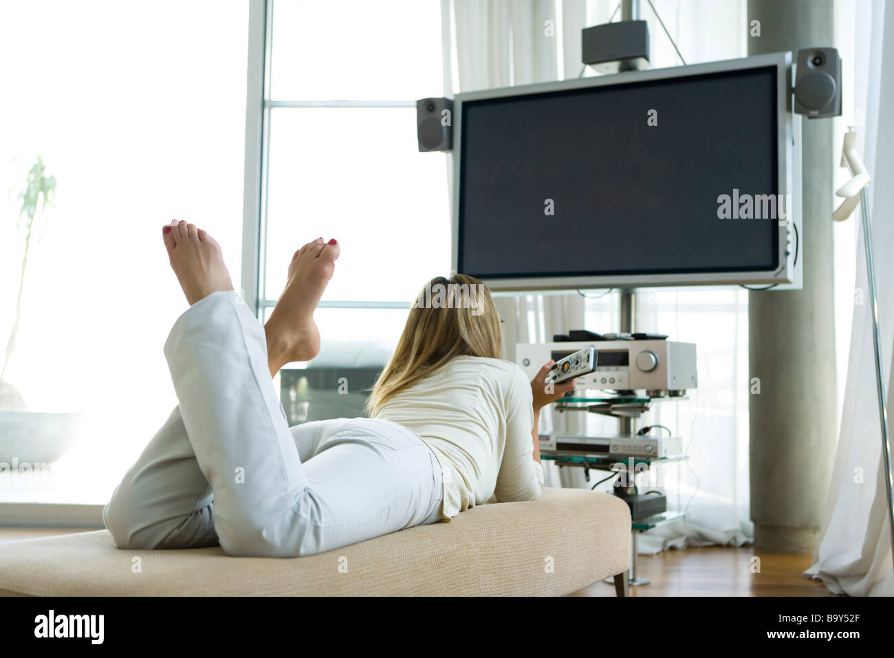Female lying on stomach watching flat screen TV with surround sound, remote control in hand, rear view - Stock Image