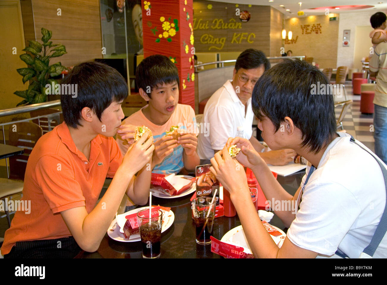 Vietnamese people eat at a KFC restaurant inside the Diamond Plaza shopping center in downtown Ho Chi Minh City - Stock Image