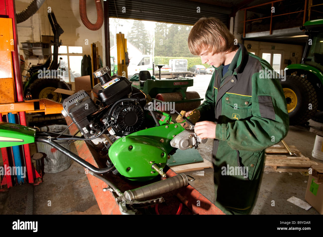 A young apprentice wearing overalls coveralls working on repairing a John Deere lawn mower in a garage workshop, - Stock Image