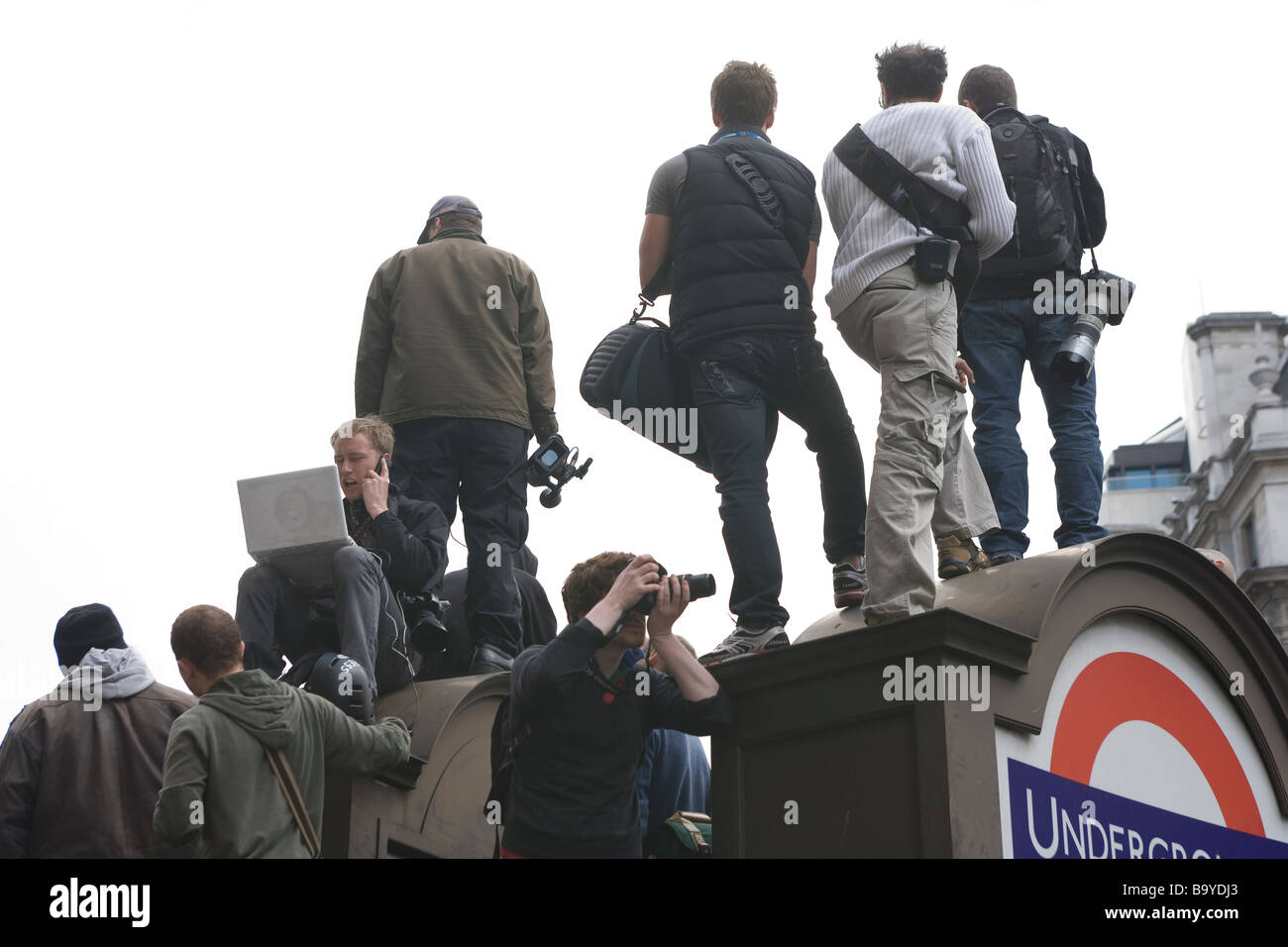 A group of reporters watching an anti capitalism protest_One is using a lap top to send a picture to his news agency - Stock Image