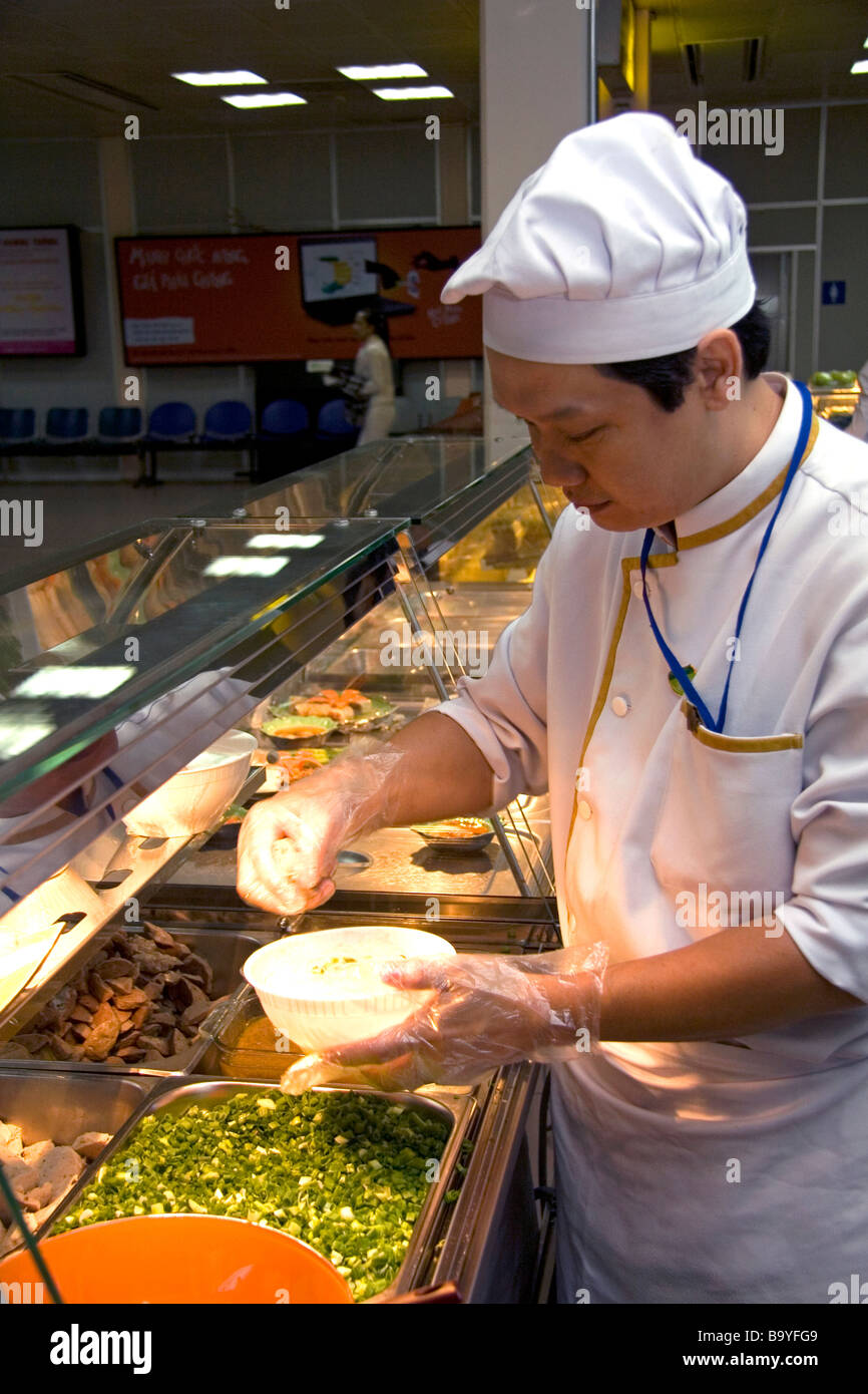 Chef making Pho Vietnamese rice noodle soup in the Tan Son Nhat International Airport serving Ho Chi Minh City Vietnam - Stock Image
