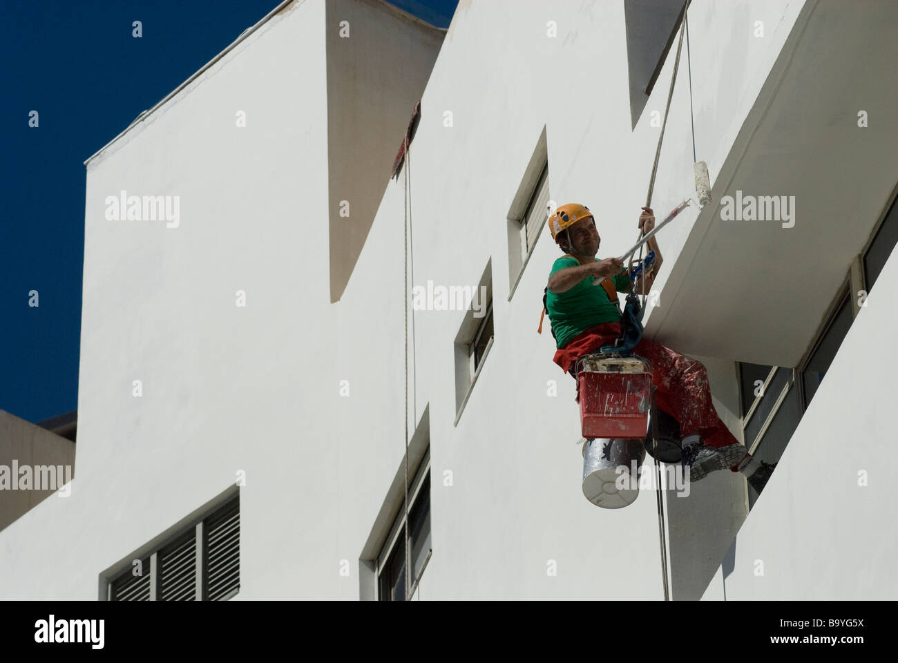 Worker Abseiling Painting Exterior Wall Of Bauhaus Style Building In - Painting-exterior-walls