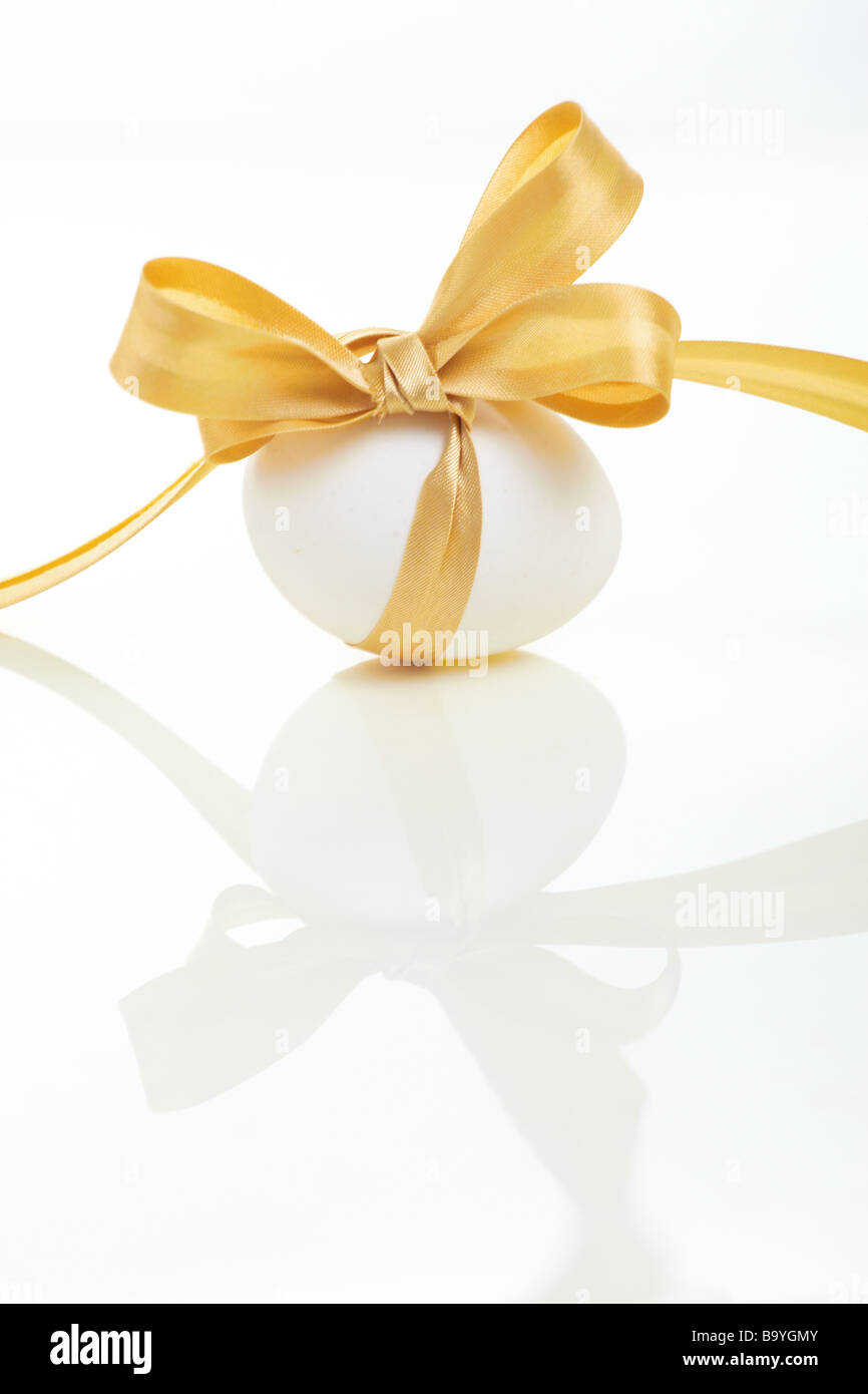 Easter egg with a bow golden - Stock Image