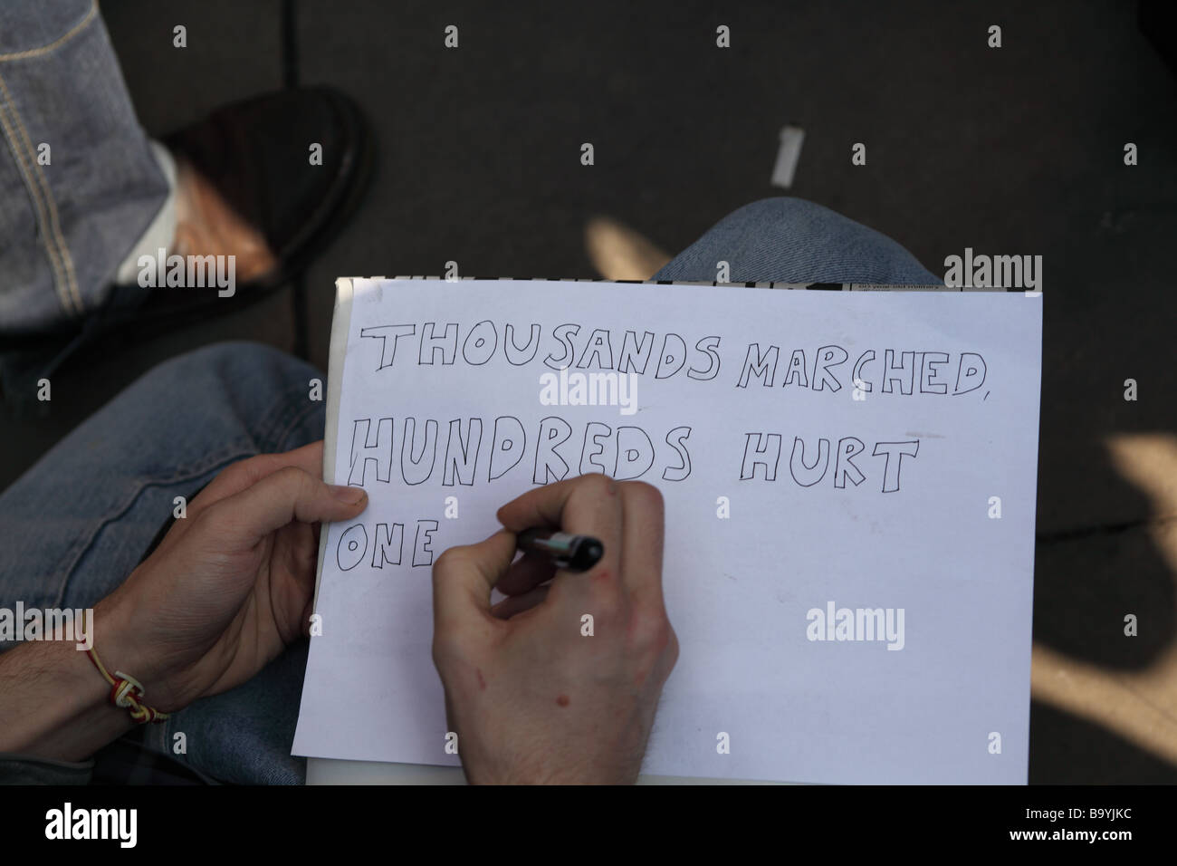 Man writing a protest message to post on a board outside the Bank of England during the 2009 G20 summit, London, - Stock Image