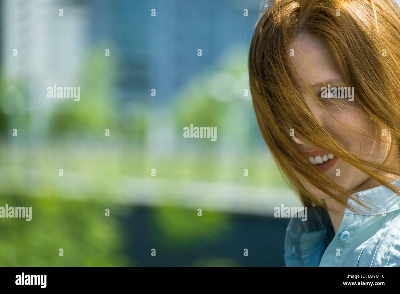 Young red haired woman with hair blowing across face, portrait - Stock Image