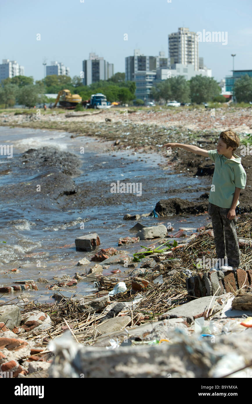Boy standing on polluted shore, looking at view, pointing - Stock Image