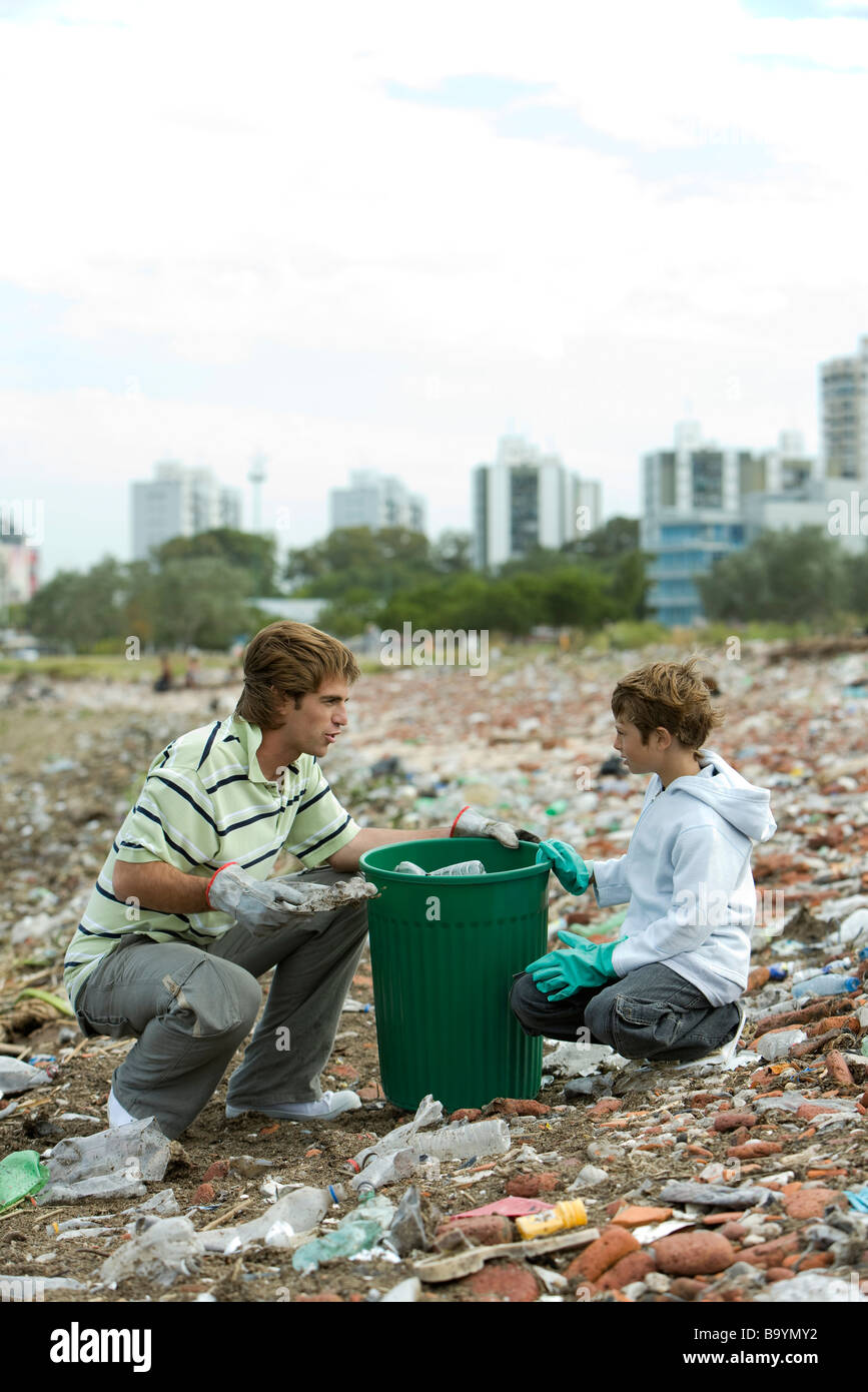 Young male and boy picking up recyclable materials in garbage heap - Stock Image
