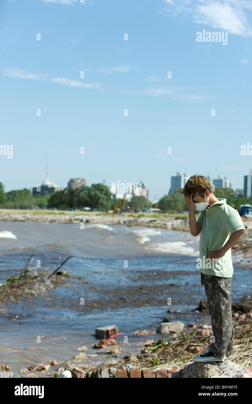 Boy standing on polluted shore, wearing pollution mask, head down - Stock Image