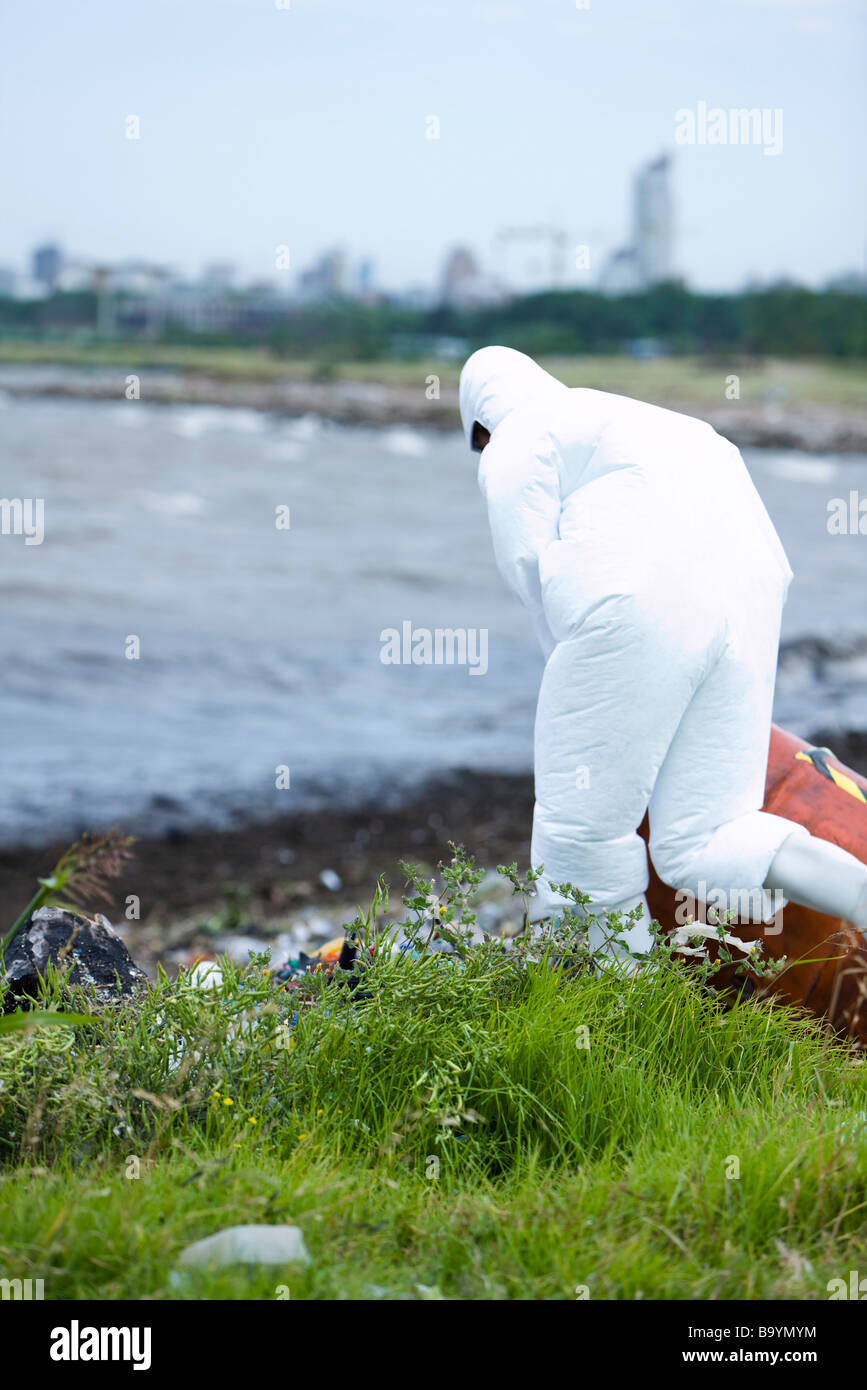 Person in protective suit cleaning up polluted shore Stock Photo