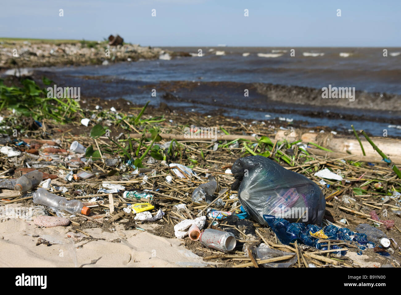 Trash washed up along shore - Stock Image