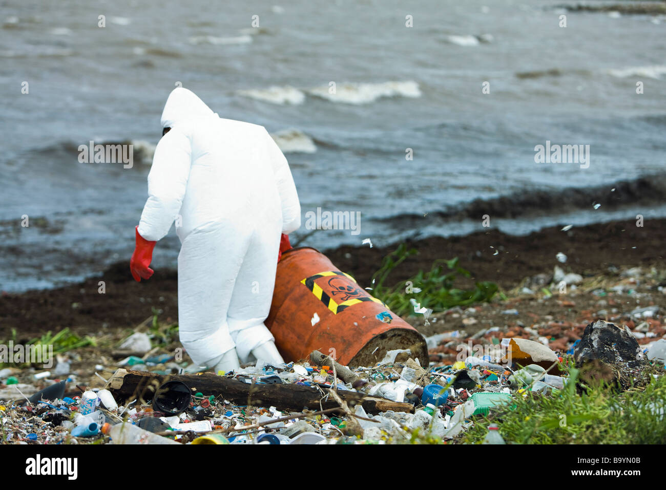Person in protective suit carrying barrel of hazardous waste on polluted shore Stock Photo