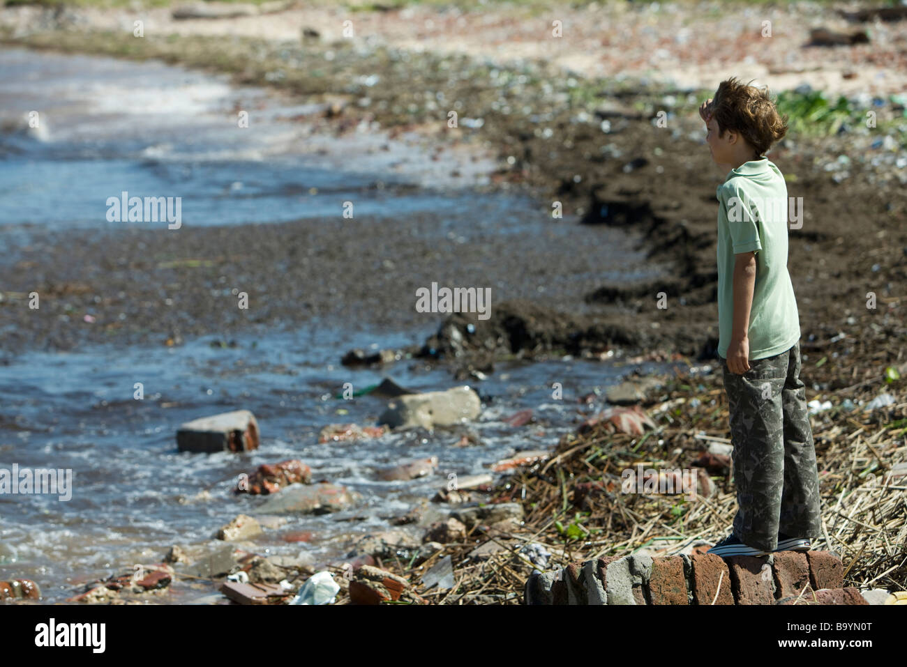 Boy standing on shore, looking out at polluted water - Stock Image