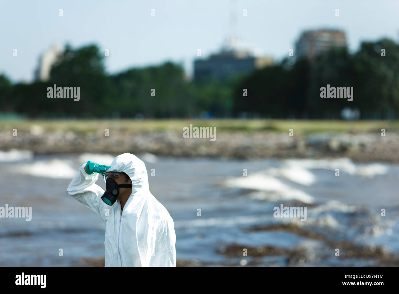 Person in protective suit looking at polluted water, side view - Stock Image