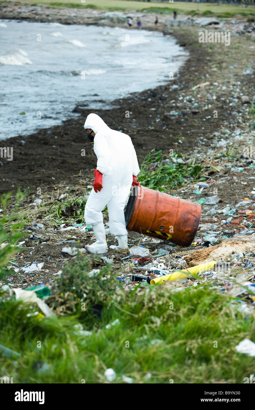Person in protective suit removing hazardous waste from polluted landscape Stock Photo