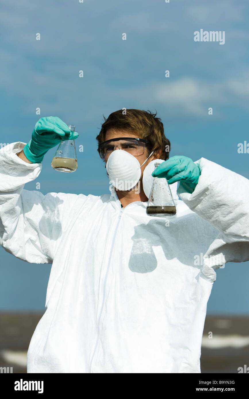 Person in protective suit holding flasks filled with polluted water - Stock Image