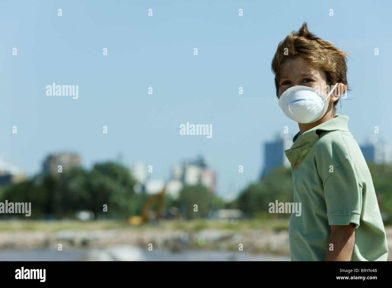 Boy standing outdoors, wearing pollution mask - Stock Image