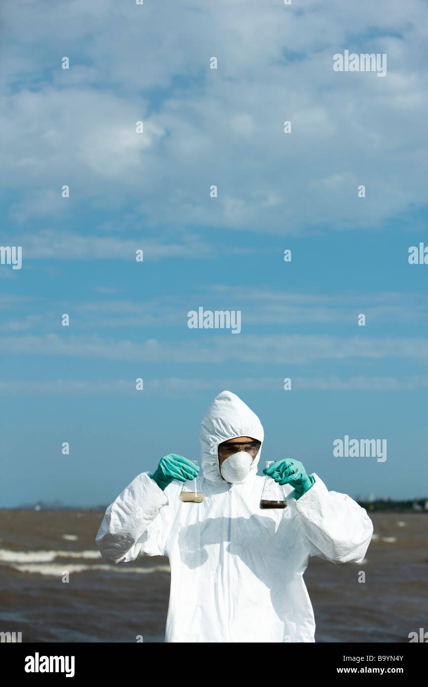 Person in protective suit holding up flasks filled with polluted water - Stock Image
