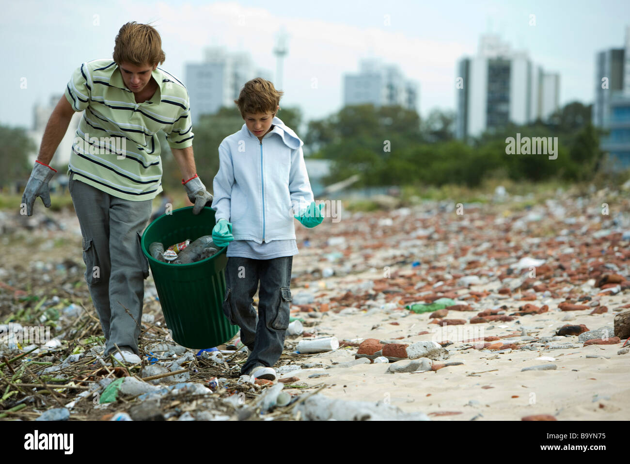 Young male and boy collecting recyclable materials in garbage dump - Stock Image