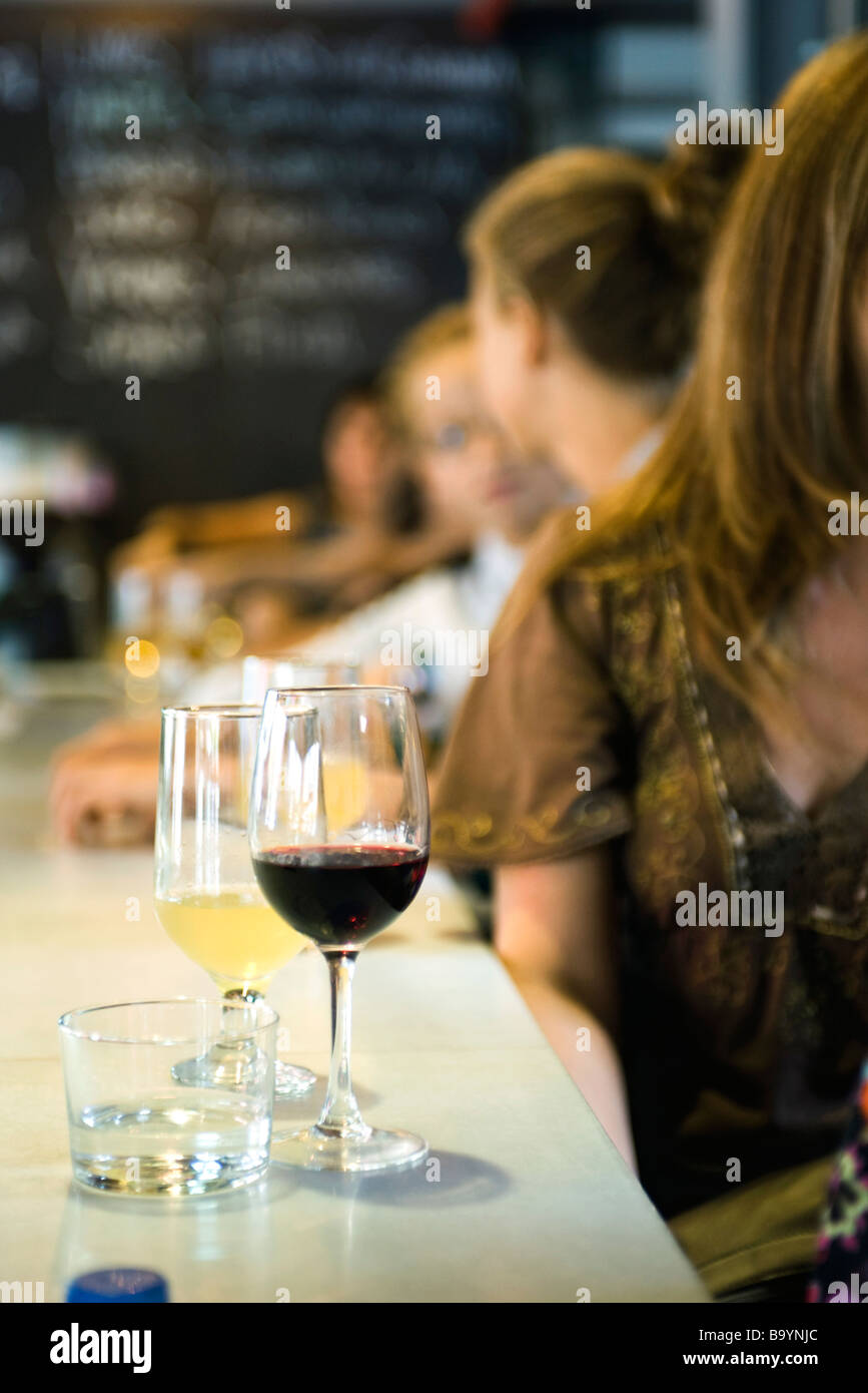 Glasses of wine set on bar, young men and women in conversation in background - Stock Image