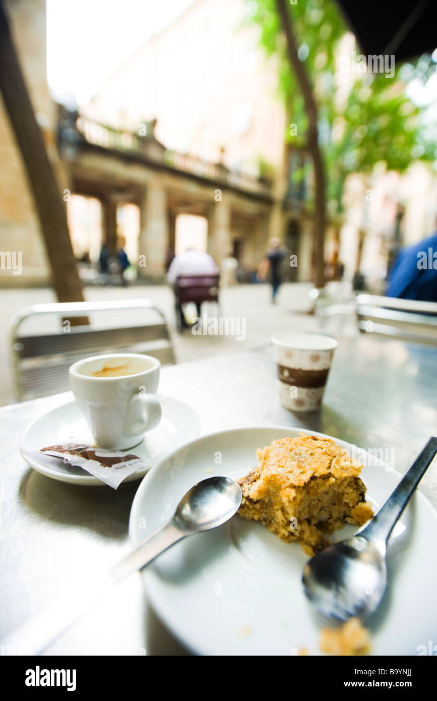 Coffee cup and half eaten pastry left on sidewalk cafe table Stock Photo