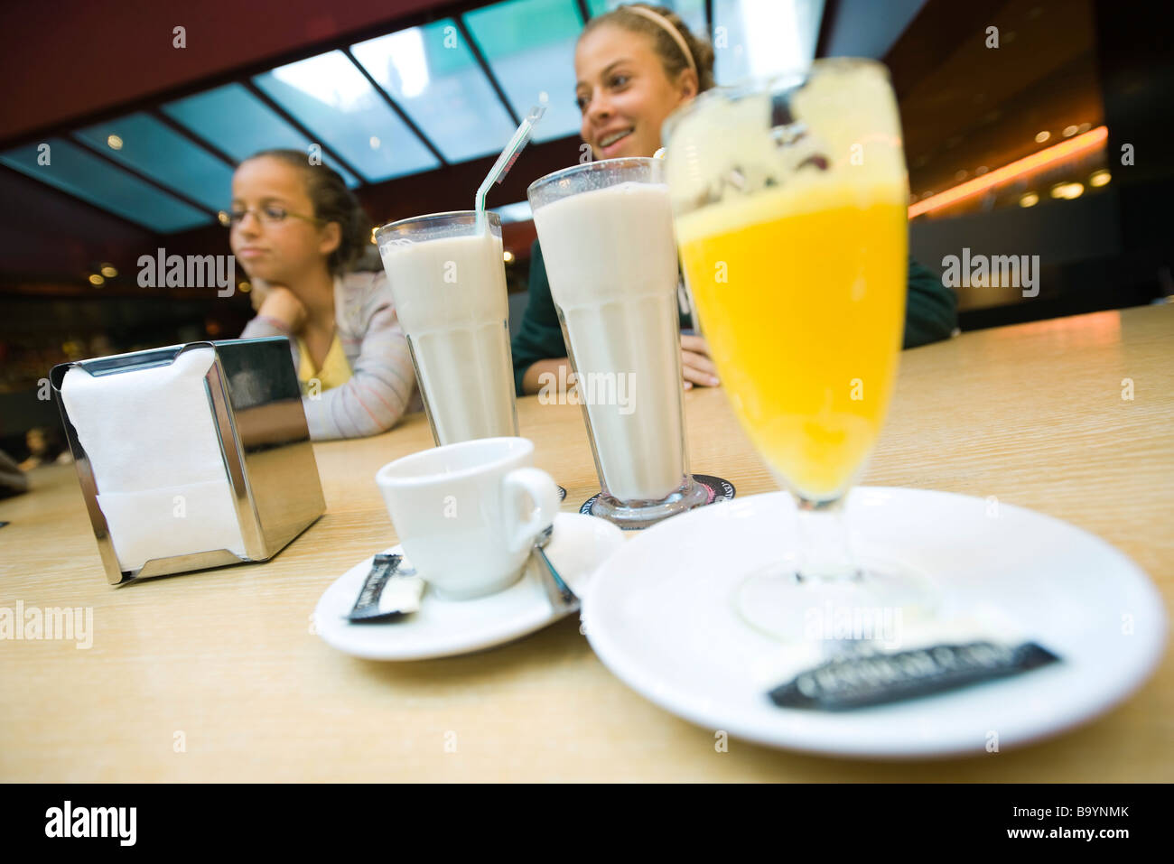 Teenage girls at cafe counter, milkshakes, glass of juice in foreground - Stock Image