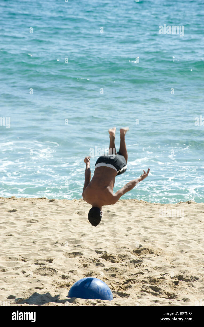 ee2b43acb5e1e6 Teen boy doing back flip on beach Stock Photo  23352082 - Alamy