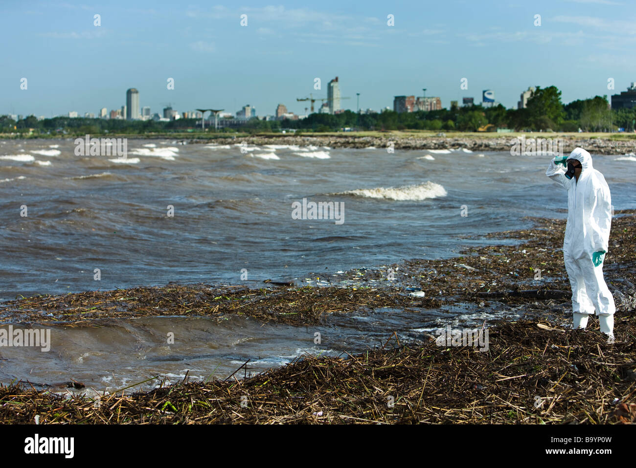 Person in protective suit standing on polluted shore, city in background - Stock Image