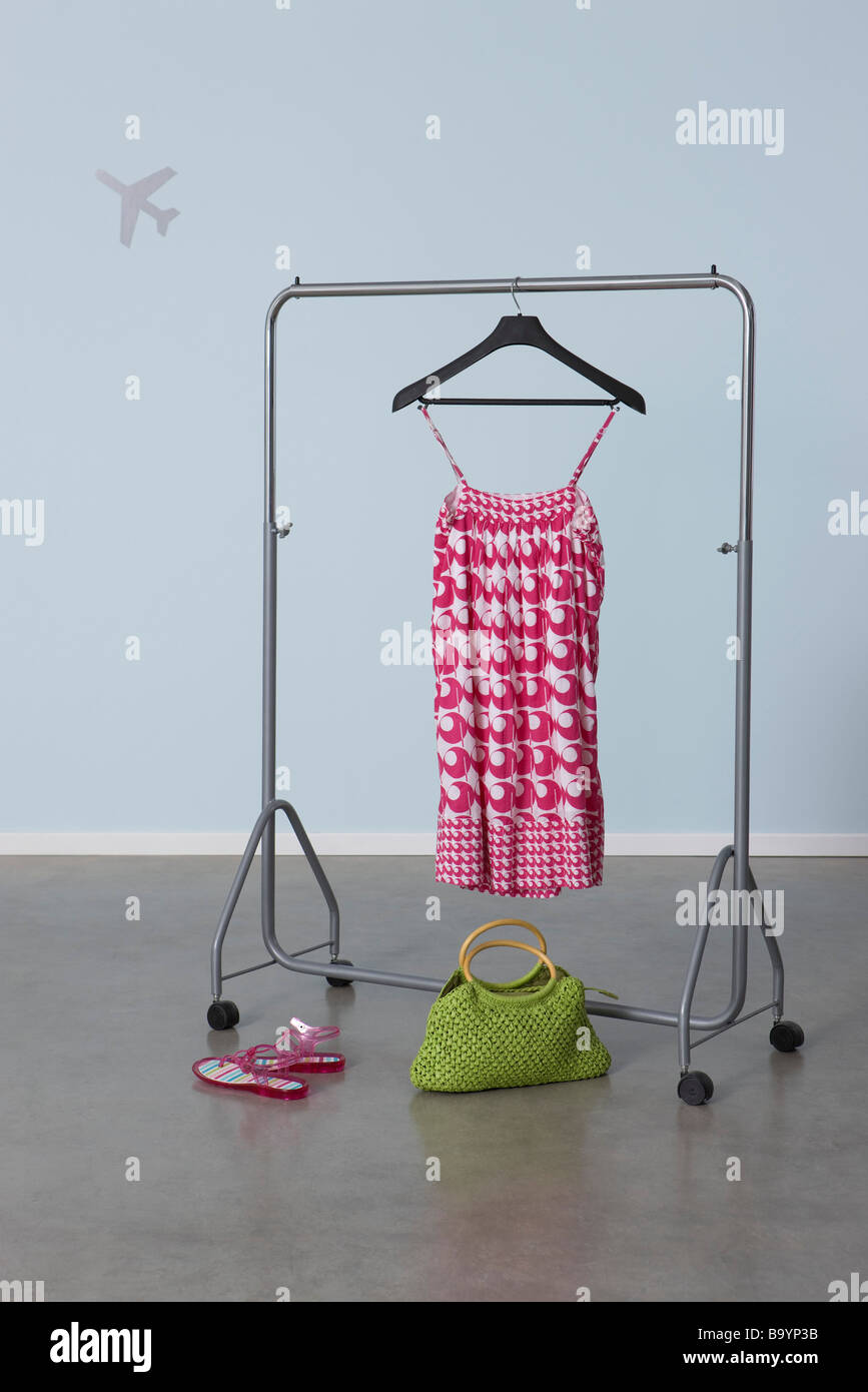 Summery woman's outfit on clothes rack, plane image in background - Stock Image