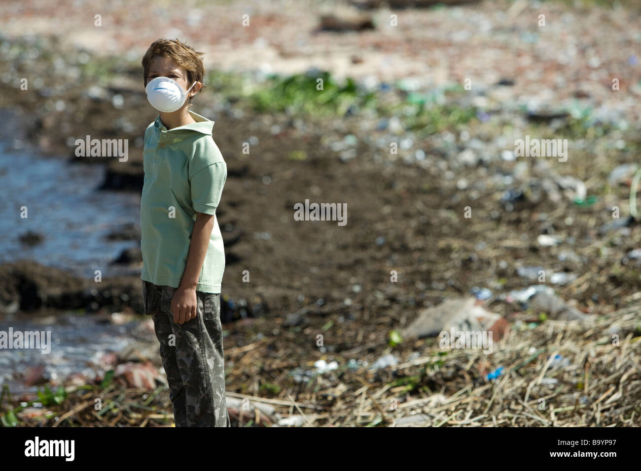 Boy standing on polluted shore, wearing pollution mask - Stock Image