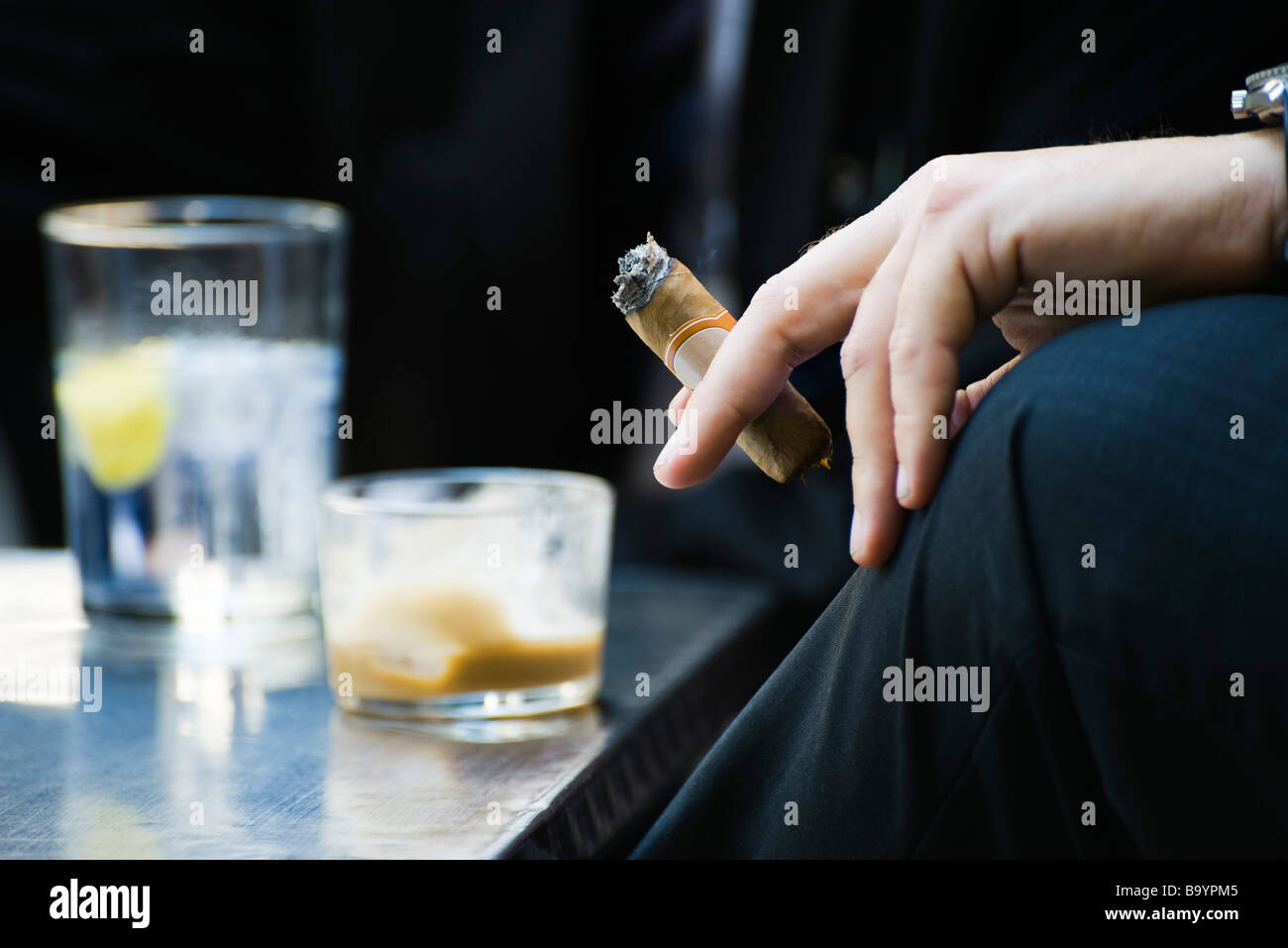 Man's hand on knee holding smoking cigar, close-up Stock Photo