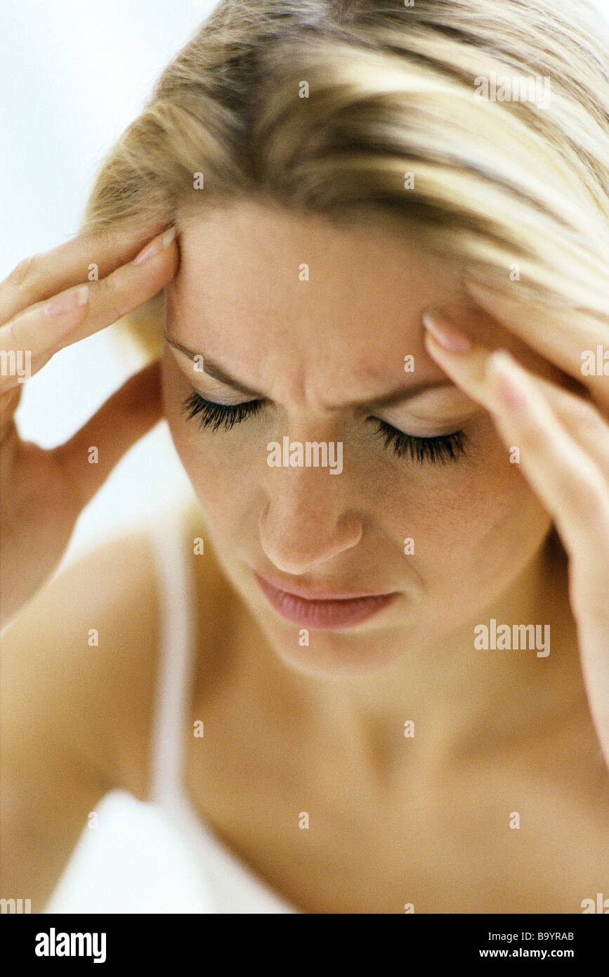 Woman furrowing brow, holding temples - Stock Image