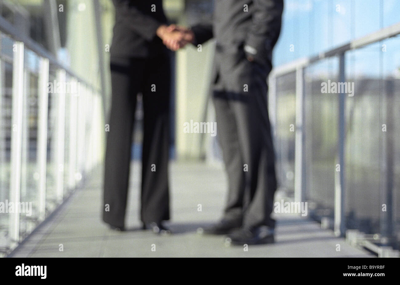 Professionals shaking hands, blurred, low section Stock Photo