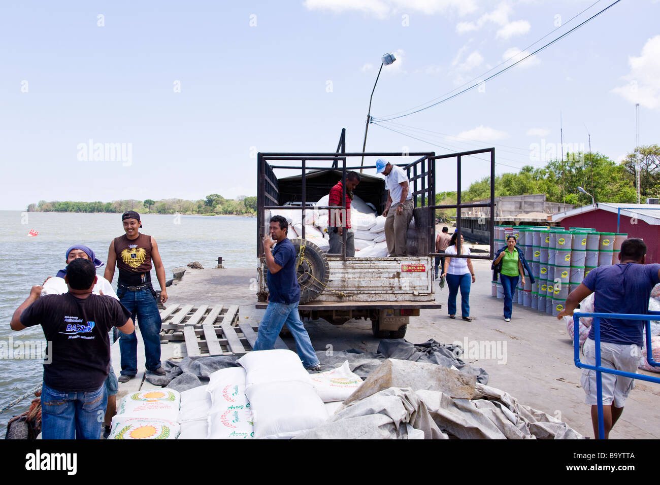 Workers loading supplies from the mainland onto a truck on the dock in Moyogalpa, Ometepe Island, Nicaragua. Stock Photo
